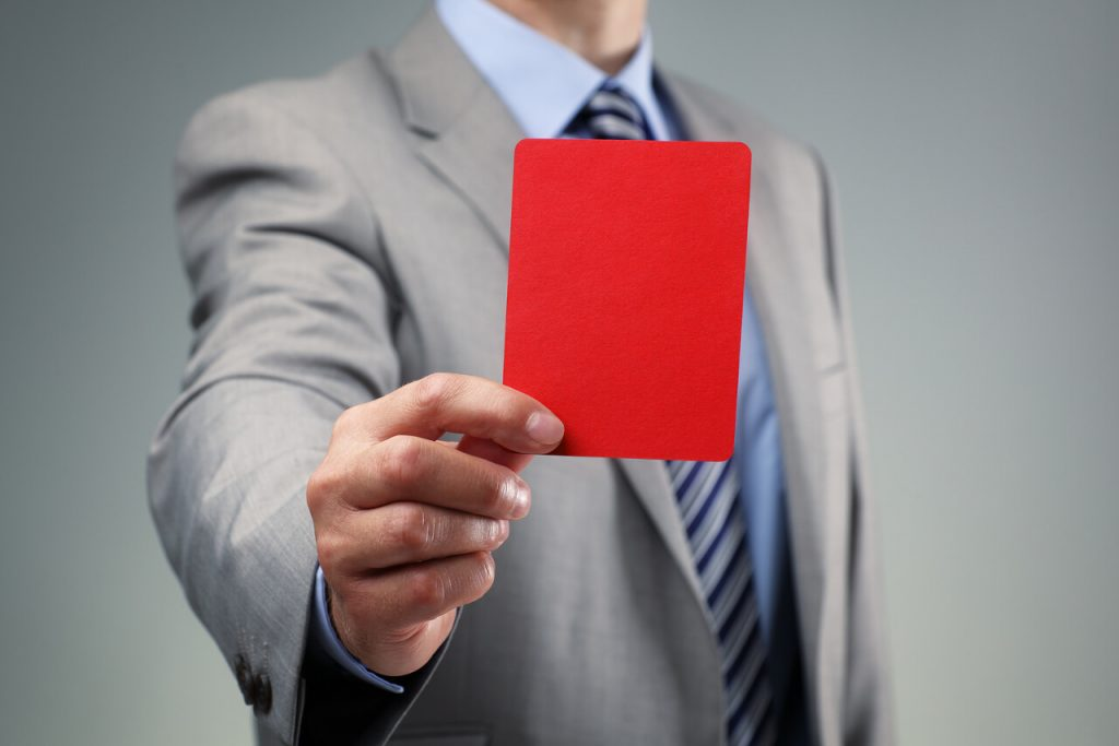 Businessman showing the red card penalty